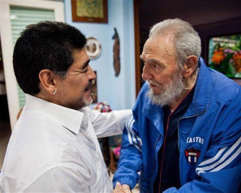 In this picture image released by Cuba's state newspaper Granma on Monday April 15, 2013, Cuba's Fidel Castro shakes hands with former soccer star Diego Maradona in Havana, Cuba, Saturday April 13, 2013. . (AP Photo/Alex Castro, Granma)