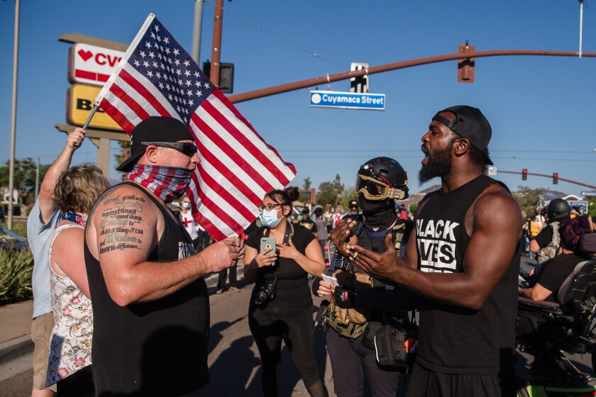 Counter-protesters and attendees speak at a protest in Santee in August 29