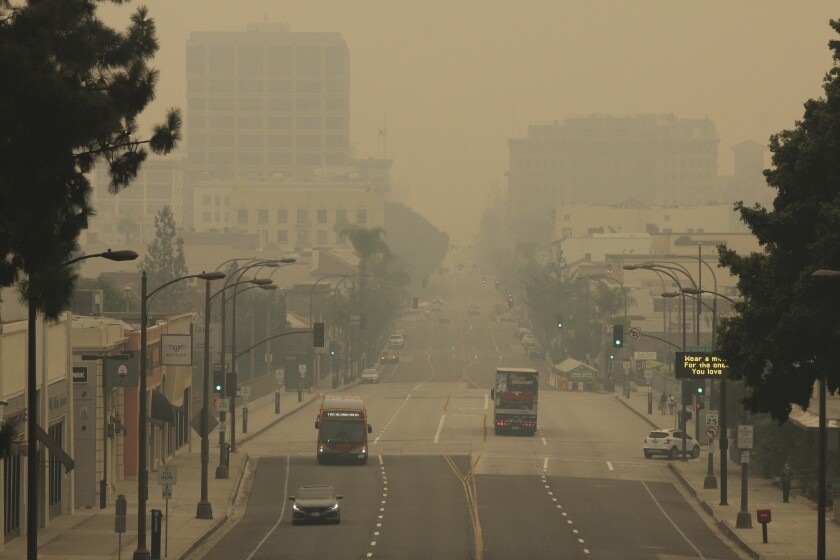 FILE - Smoke from wildfires fills the sky over Pasadena, Calif., in this view looking east down Colorado Boulevard in a Saturday, Sept. 12, 2020 file photo. The fires consuming the forests of California and Oregon and darkening the skies over San Francisco and Portland are also damaging an economy already struggling with the coronavirus outbreak. In the communities where they are raging, wildfires are destroying property, running up huge losses for property insurers and putting a strain on economic activity that could linger for a year or more. (AP Photo/John Antczak, File)