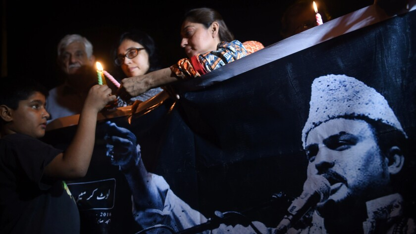 """Pakistani activists light candles in Karachi as thousands crowd the streets for the funeral of Sufi musician Amjad Sabri, who was gunned down in what police called an """"act of terror."""""""
