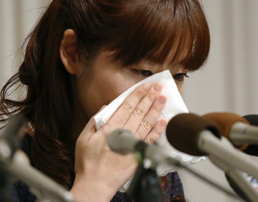 Embattled stem cell researcher Haruko Obokata wipes away a tear while answering questions about her controversial research on STAP cells.