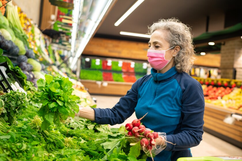 woman looks at produce in grocery store