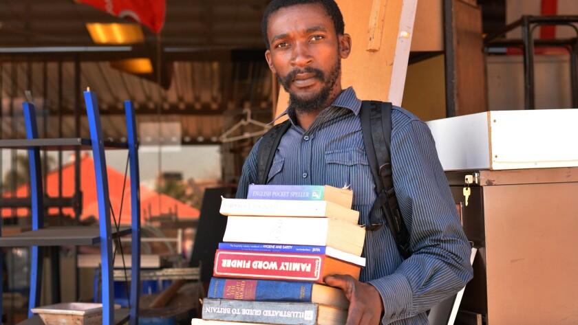 Sandile Mavimbela sells books from his makeshift sidewalk shop in Johannesburg, South Africa.