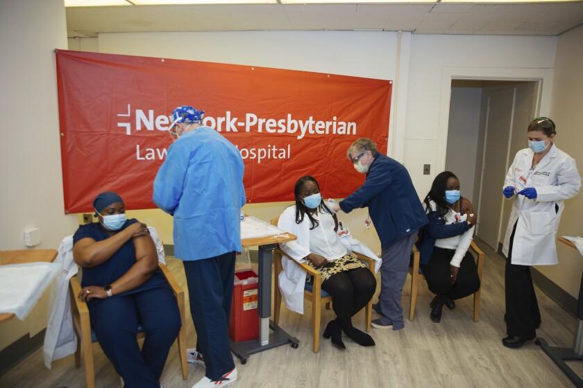 personal médico inyectando a las hermanas Claudia Scott-Mighty (izquierda) y Althea Scott-Bonaparte,