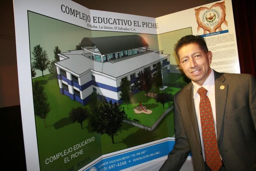 Enot Rubio, presidente de el Comite El Piche, posa junto al material publicitario del complejo educativo a construirse en el oriente de El Salvador.