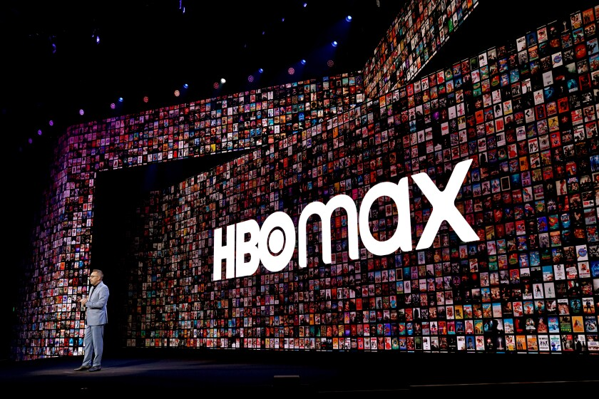 WarnerMedia executive Tony Goncalves stands before a giant HBO Max logo.