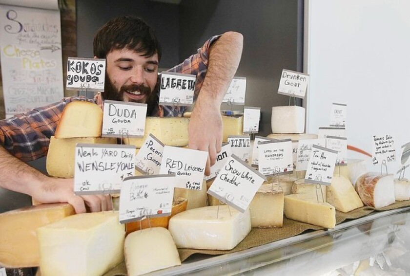 Max Frederick, the manager of The Cheese Shop at OC Mix puts away chesse on Monday.