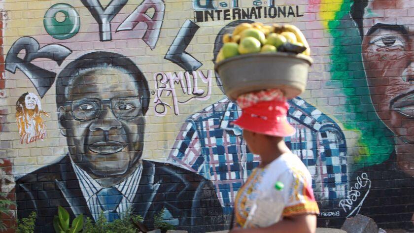 A woman walks past a painting of Zimbabwean President Robert Mugabe in Harare, Monday, Nov, 20, 2017