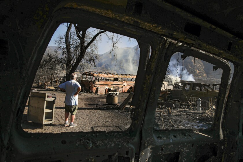 Tim Handman surveys damage to his property caused by the fast-moving South fire.