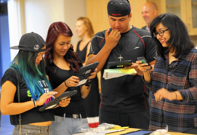 Students Jordann Ventura, 14, left, Karyna Mills, 15, Guillermo Romero, 15, and Dayanara Trujillo, 15, try out their iPads in pre-first-day orientation at Valley Academy of Arts and Sciences in Granada Hills.