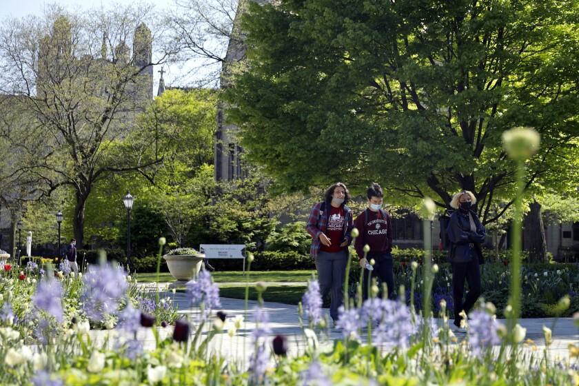 Estudiantes luciendo mascarillas caminan por el campus de la Universidad de Chicago el 6 de mayo del 2021.