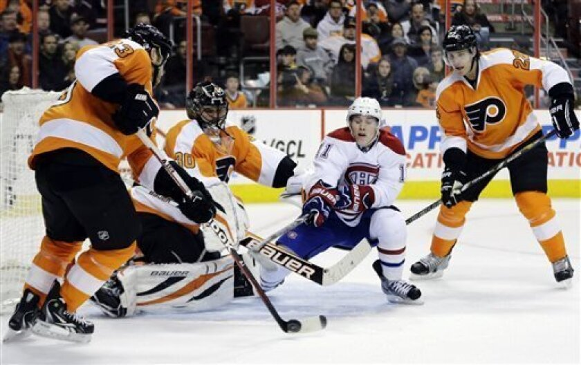 Montreal Canadiens' Brendan Gallagher, center, tries to grab a loose puck against Philadelphia Flyers' Kent Huskins, left, goalie Ilya Bryzgalov, of Russia, and Luke Schenn during the first period of an NHL hockey game, Wednesday, April 3, 2013, in Philadelphia. (AP Photo/Matt Slocum)
