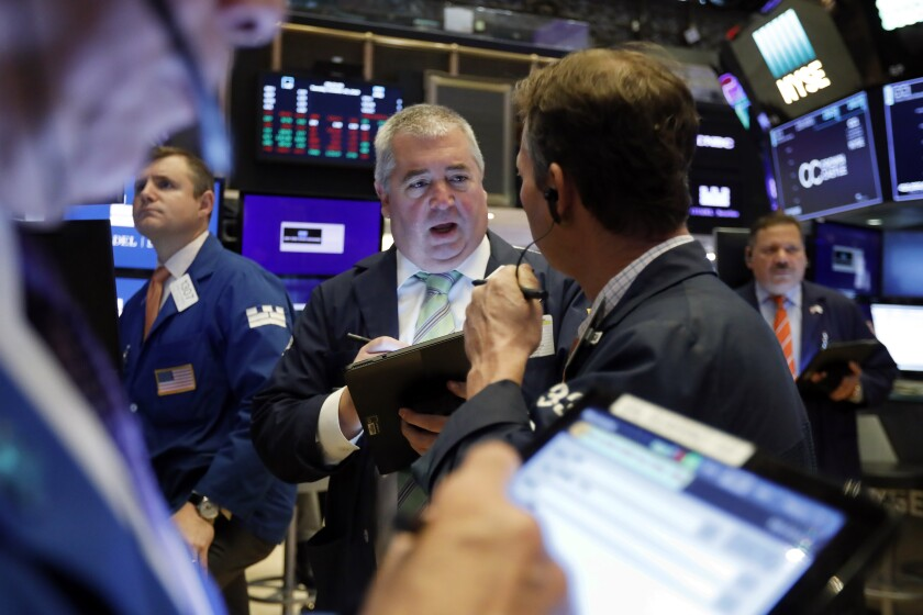 FILE - In this Oct. 29, 2019, file photo Edward McCarthy, center, works with fellow traders on the floor of the New York Stock Exchange. The U.S. stock market opens at 9:30 a.m. EST on Monday, Nov 4. (AP Photo/Richard Drew, File)