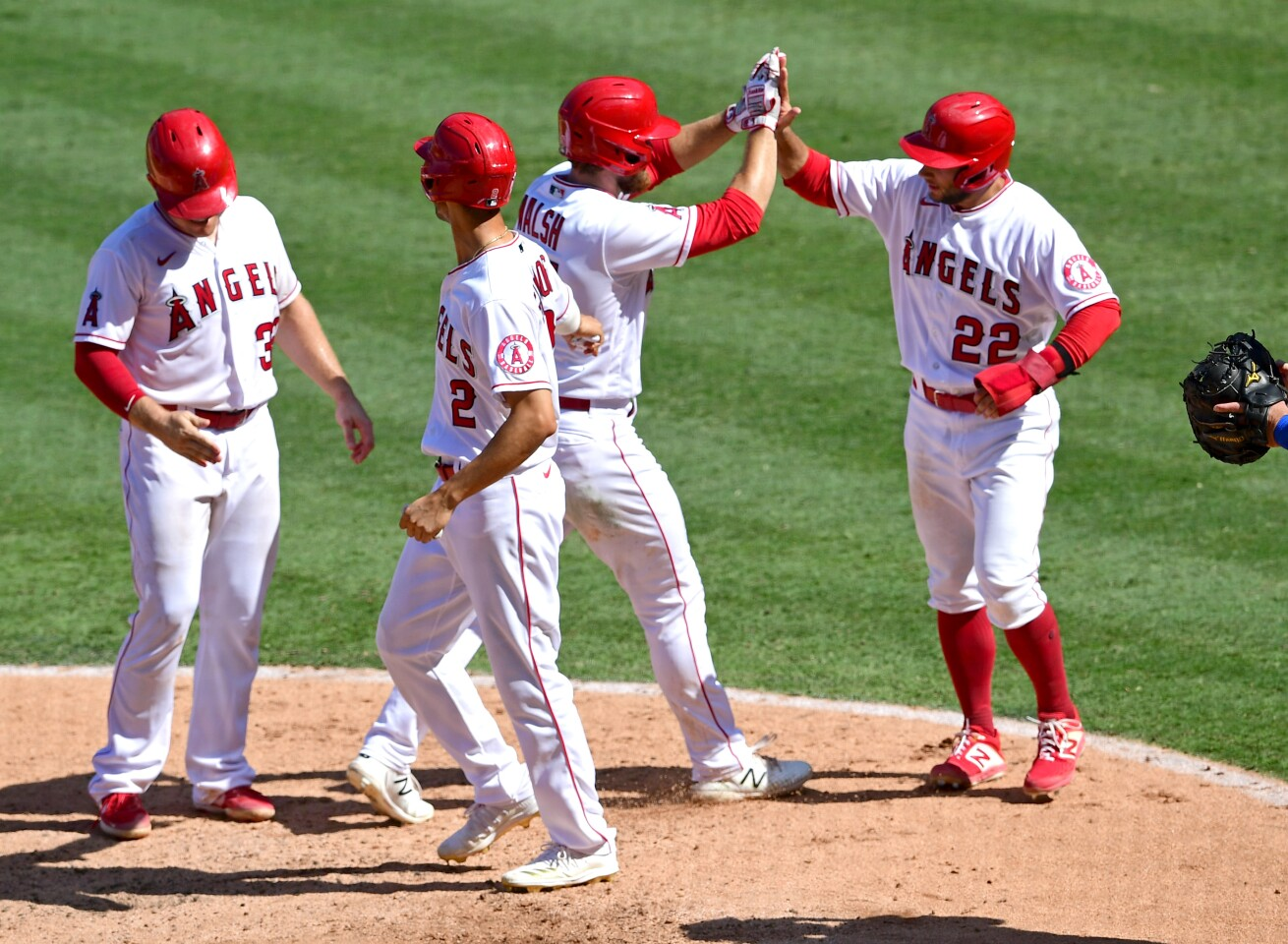 ANAHEIM, CA - SEPTEMBER 21: Jared Walsh #25 is congratulated by Max Stassi #33, Andrelton Simmons #2 and David Fletcher #22 of the Los Angeles Angels after hitting a grand slam home run in the fourth inning of the game against the Texas Rangers at Angel Stadium of Anaheim on September 21, 2020 in Anaheim, California. (Photo by Jayne Kamin-Oncea/Getty Images)