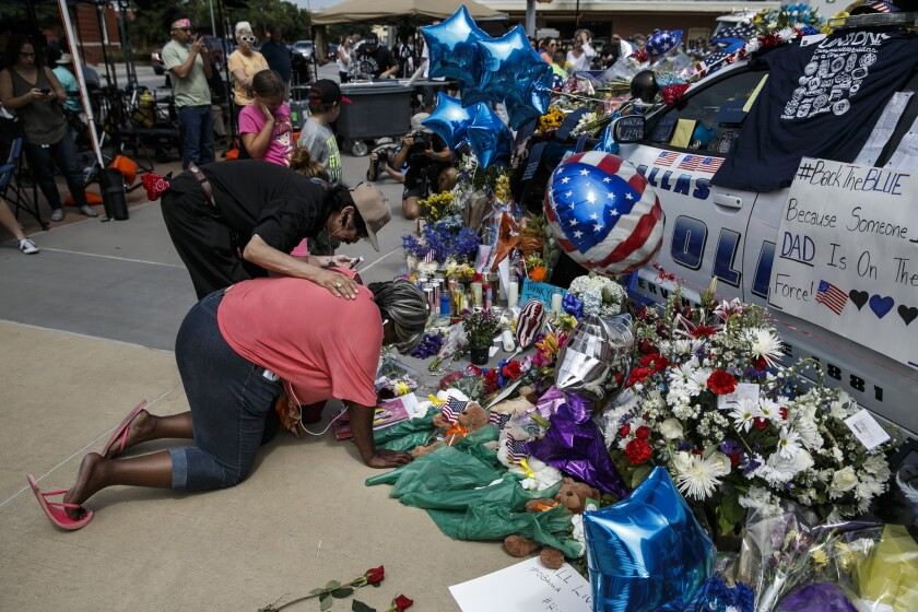 Djuana Franklin is consoled by a passerby as she weeps at the memorial for slain police officers in Dallas.