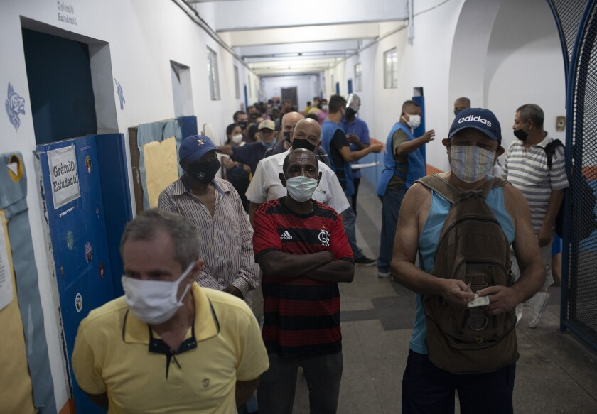 People wait in line to vote in municipal elections at a polling station at the Rocinha slum of Rio de Janeiro, Brazil, Sunday, Nov.15, 2020. Voters across Latin America's biggest country are electing mayors and municipal council members. (AP Photo/Silvia Izquierdo)
