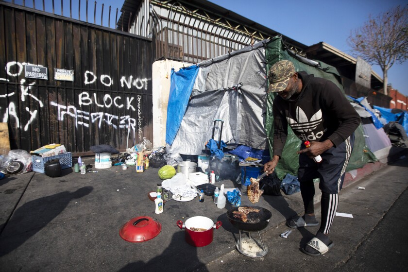 Anthony Curry cooks outside his tent in the skid row area