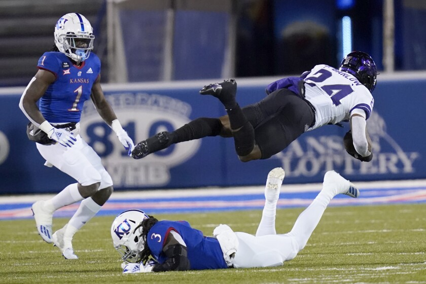 TCU running back Darwin Barlow (24) dives over Kansas safety Ricky Thomas (3) during the first half of an NCAA college football game in Lawrence, Kan., Saturday, Nov. 28, 2020. (AP Photo/Orlin Wagner)