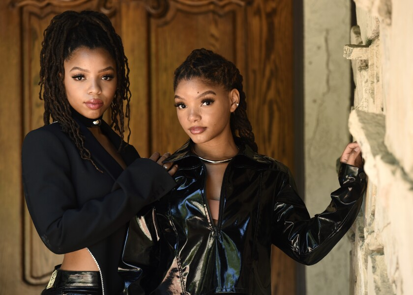 """In this May 28, 2020 photo, Chloe Bailey, left, and her sister Halle Bailey, of the R&B duo Chloe X Halle, pose for a portrait in their backyard in Los Angeles to promote their latest release, """"Ungodly Hour."""" (AP Photo/Chris Pizzello)"""