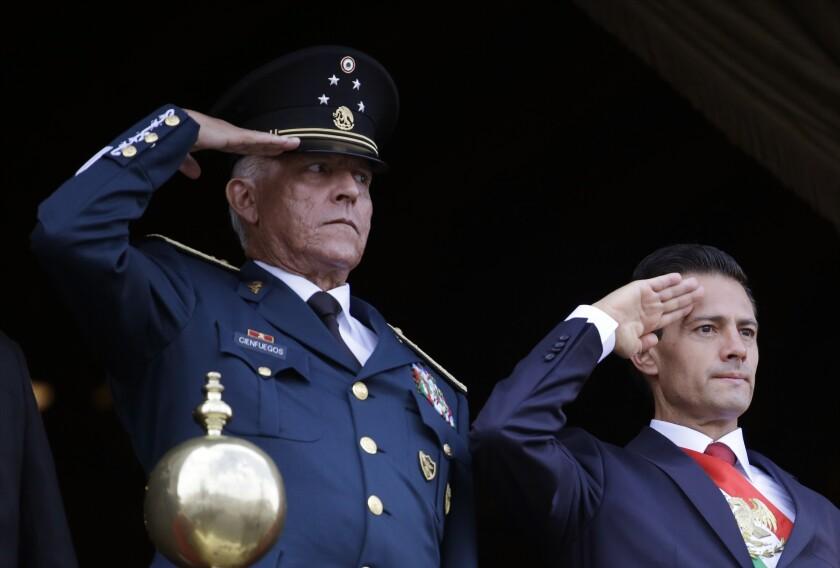 Mexican Defense Secretary Gen. Salvador Cienfuegos Zepeda, left, and President Enrique Peña Nieto, salute at a parade.