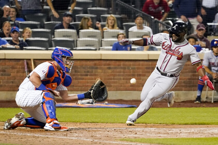 New York Mets catcher James McCann tags out Atlanta Braves' Abraham Almonte off a pinch hit from Ehire Adrianza during the ninth inning of a baseball game, Wednesday, July 28, 2021, in New York. The Mets won 2-1. (AP Photo/Mary Altaffer)
