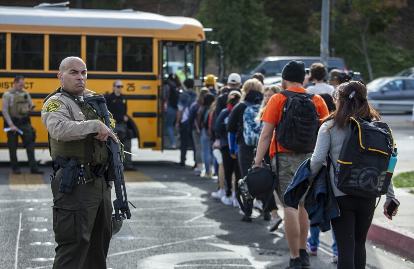 Students evacuated from Saugus High School board buses to be taken to a reunification area after the shooting in Santa Clarita, Calif.