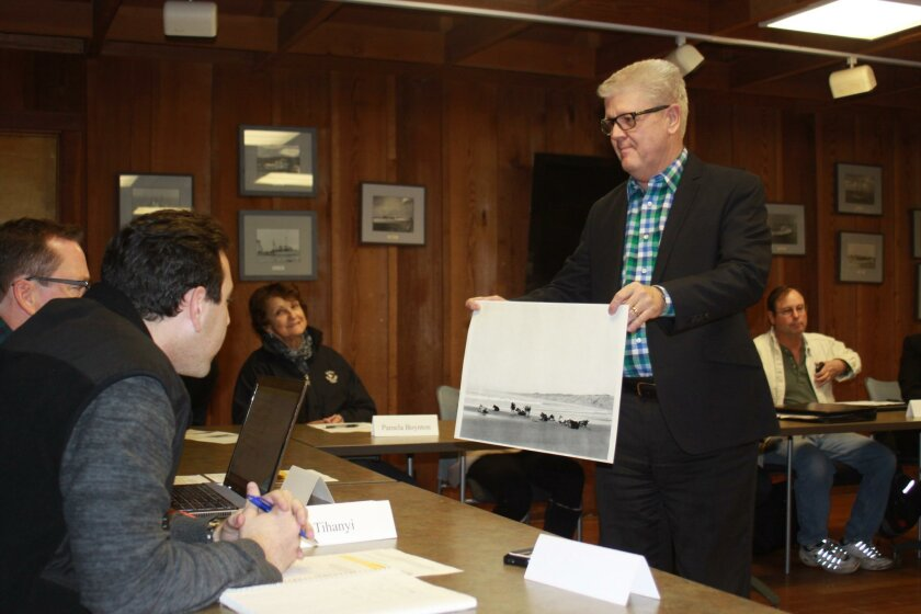 La Jolla Historical Society executive director Heath Fox shows an enlargement of the 1906 photo of cows on the beach. The Society will re-create the photo in March to mark its 110th anniversary.