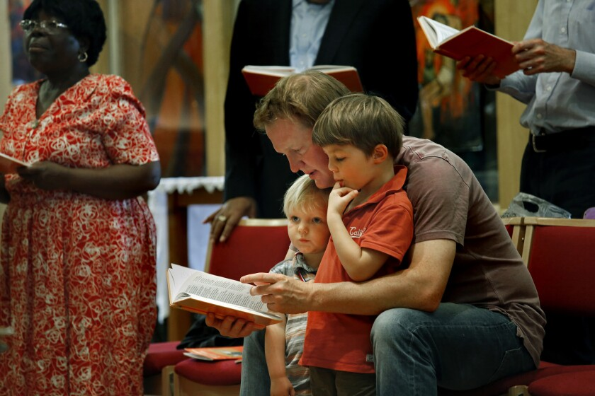 Tom Catchpole, age 34, and his two children Rufferty, age 2, and Percy, age 4, right, attend St. Matthew's Brixton Church in Braxton on Sunday, June 26, 2016.
