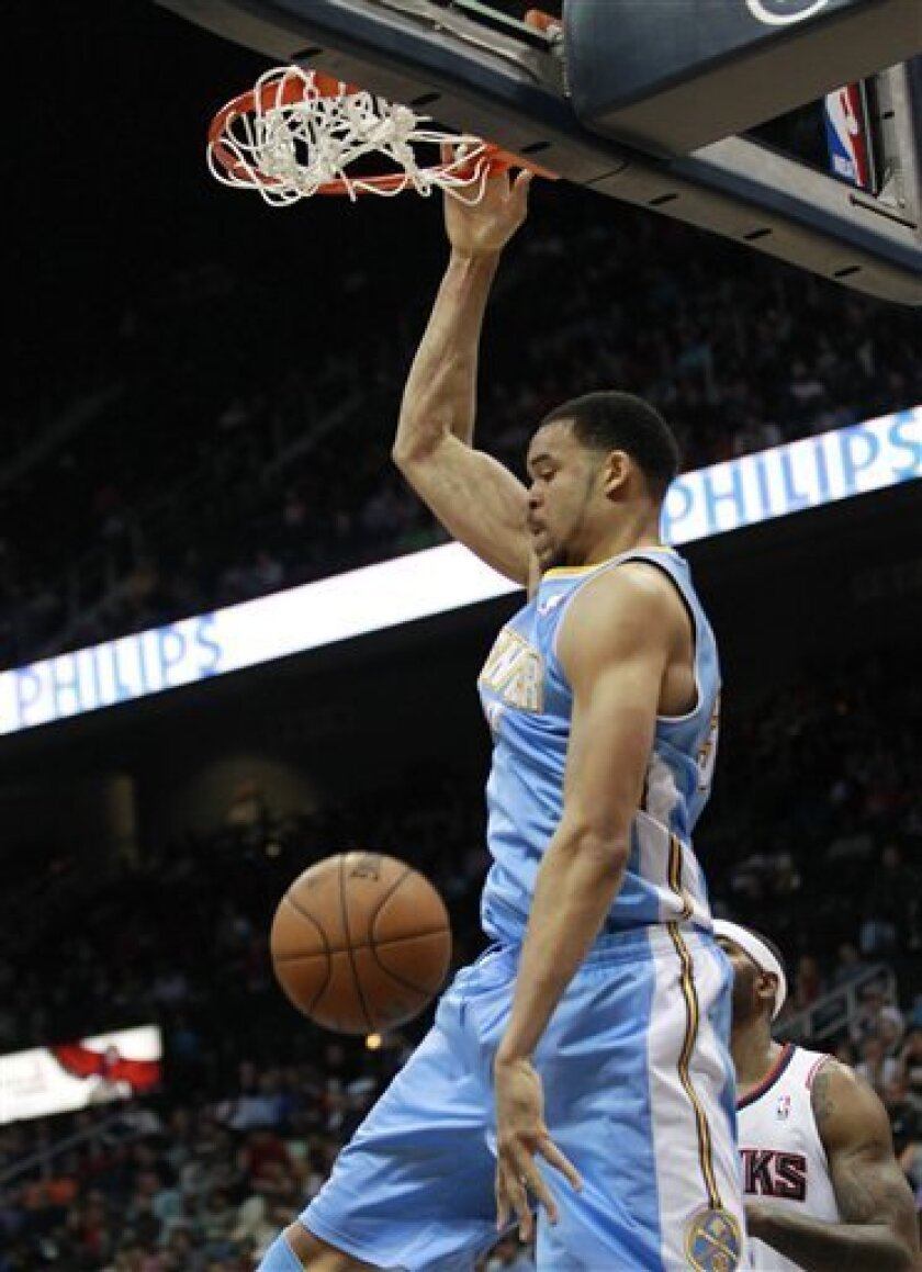 Denver Nuggets center JaVale McGee, top, scores during the second half of an NBA basketball game against the Atlanta Hawks, Wednesday, Dec. 5, 2012, in Atlanta. (AP Photo/John Bazemore)