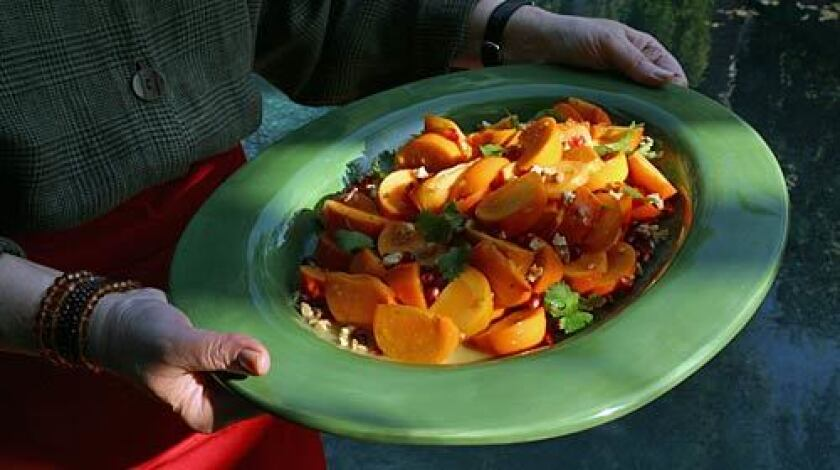 Fuyu persimmons with cumin-lime dressing and pomegranates.