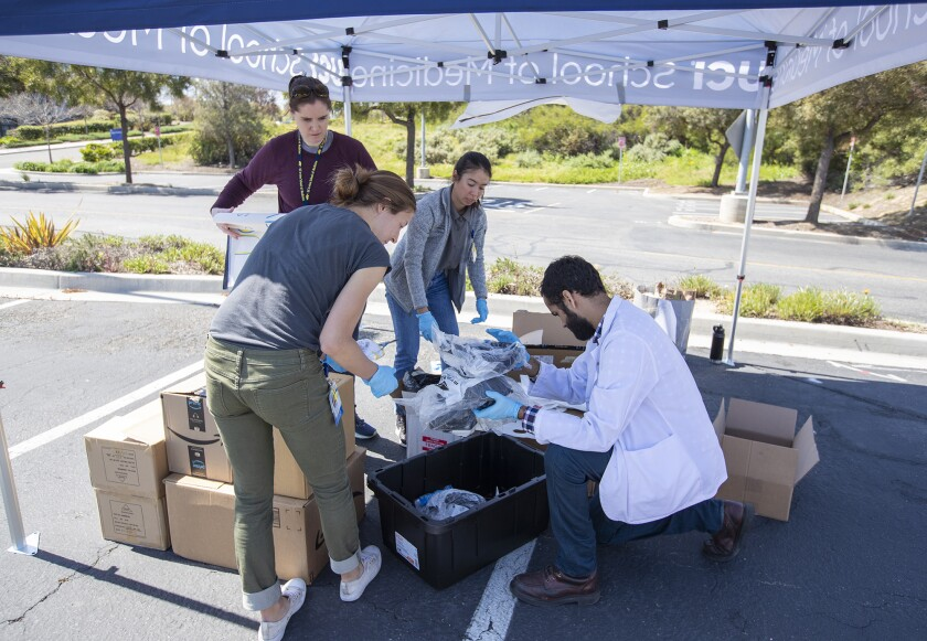 UC Irvine medical students, clockwise from front, Alexandra Bray, Jessica Sea, Catriona Lewis and Jaspal Bassi organize personal protective equipment such as masks, sanitizer, gloves and other supplies donated for medical workers Monday during a collection in Irvine.