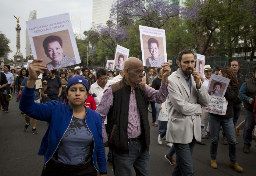 People hold photos of Mexican journalist Miroslava Breach, gunned down in March 2017 in the northern