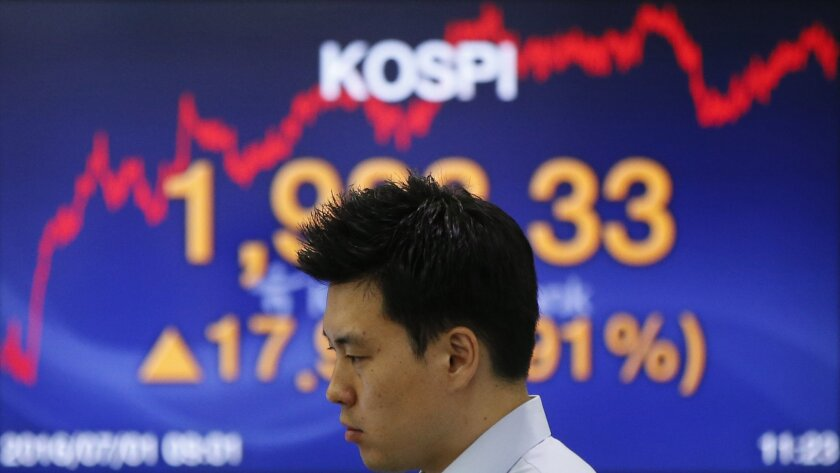 A currency trader looks at the monitors near a screen showing the Korea Composite Stock Price Index (KOSPI) at the foreign exchange dealing room in Seoul, South Korea, Friday, July 1, 2016. Asian shares mostly rose Friday with investors remaining in a buying mood amid low interest rates and after w