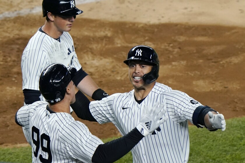 New York Yankees Aaron Judge, (99) celebrates with designated hitter Giancarlo Stanton after scoring on Stanton's fifth-inning grand slam in a baseball game against the Baltimore Orioles, Monday, April 5, 2021, at Yankee Stadium in New York. Yankees' DJ LeMahieu passes behind the pair. (AP Photo/Kathy Willens)