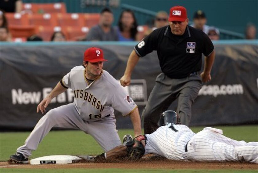 Florida Marlins' Emilio Bonifacio, bottom right, is tagged out by Pittsburgh Pirates third baseman Andy LaRoche (15) in the third inning of a baseball game as third base umpire Mike Carlson, upper right, watches the play in Miami, Saturday, July 4, 2009. (AP Photo/Alan Diaz)
