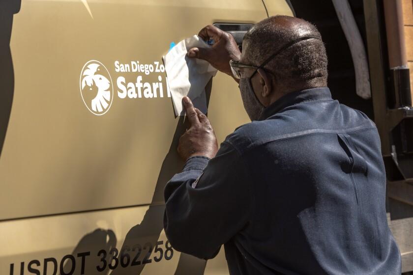 San Diego Zoo Safari Park senior mechanic Darrell Jennings installs a new logo on a vehicle.