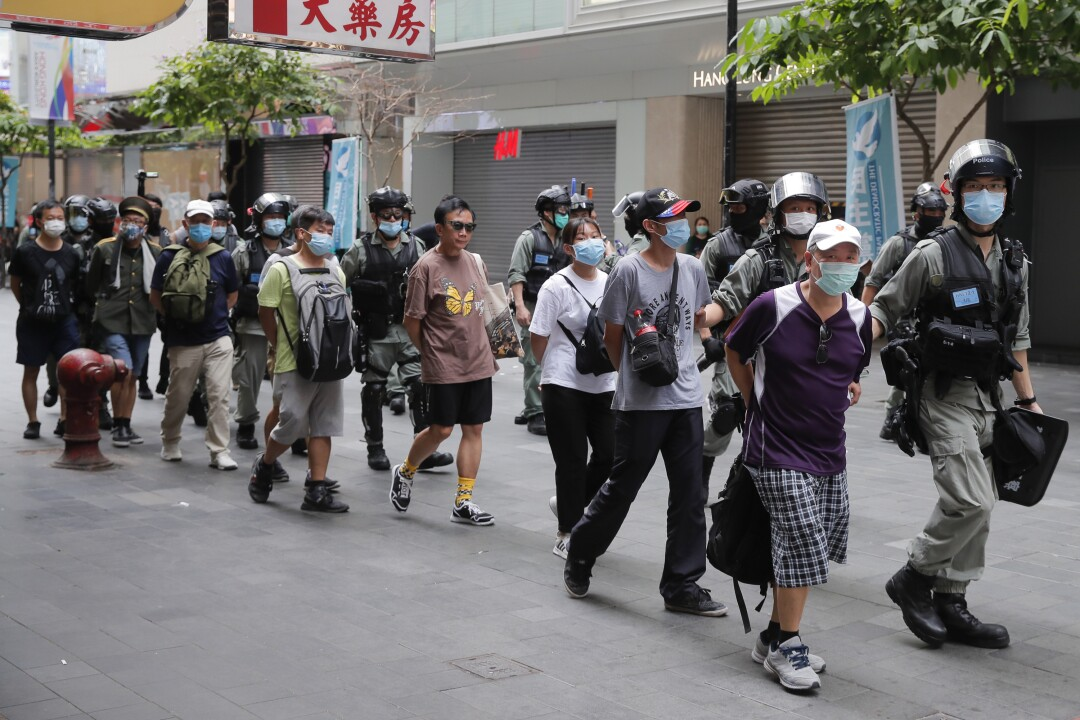 Police detain protesters after a protest in Causeway Bay before the annual handover march in Hong Kon