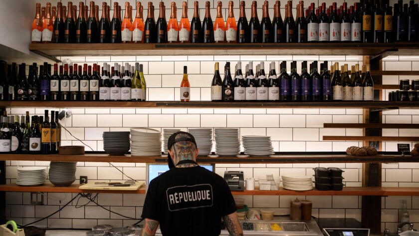 An employee prepares food as bottles of wine stand on shelves at Republique restaurant.