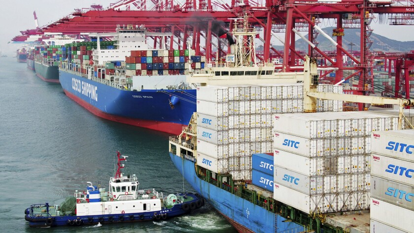 In this Wednesday, May 8, 2019, photo, a barge pushes a container ship to the dockyard in Qingdao in