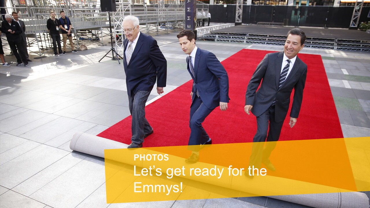 Andy Samberg, host of the 2015 Emmy Awards, center, rolls out the red carpet with executive producer Don Mischer, left, and Television Academy Chairman/CEO Bruce Rosenblum during a press preview three days before the show.