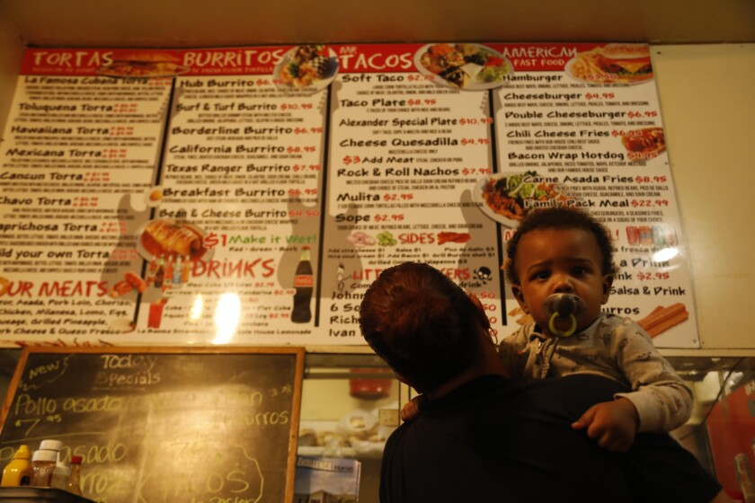 Yvelisse Cotto holds her 18-month-old grandson, Jase Carter, while trying to decide what to order.
