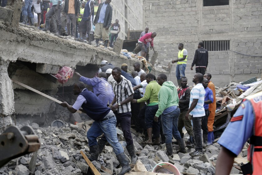 People at the scene of a collapsed building in in Tasia Embakasi, an east neighbourhood of Nairobi, Kenya on Friday Dec. 6, 2019. A six-story building collapsed in Kenya's capital on Friday, officials said, with people feared to be trapped in the debris. Police say people have been rescued by residents using their bare hands. (AP Photo/Khalil Senosi)