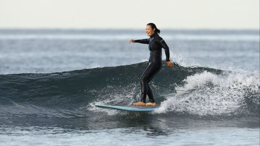 San Diego native Tiffany Joh is a veteran on the LPGA Tour, and an avid surfer, shown here Tuesday morning in Carlsbad. Joh will play at the Kia Classic this week at Aviara, but is glad to be home to catch some waves in between rounds.