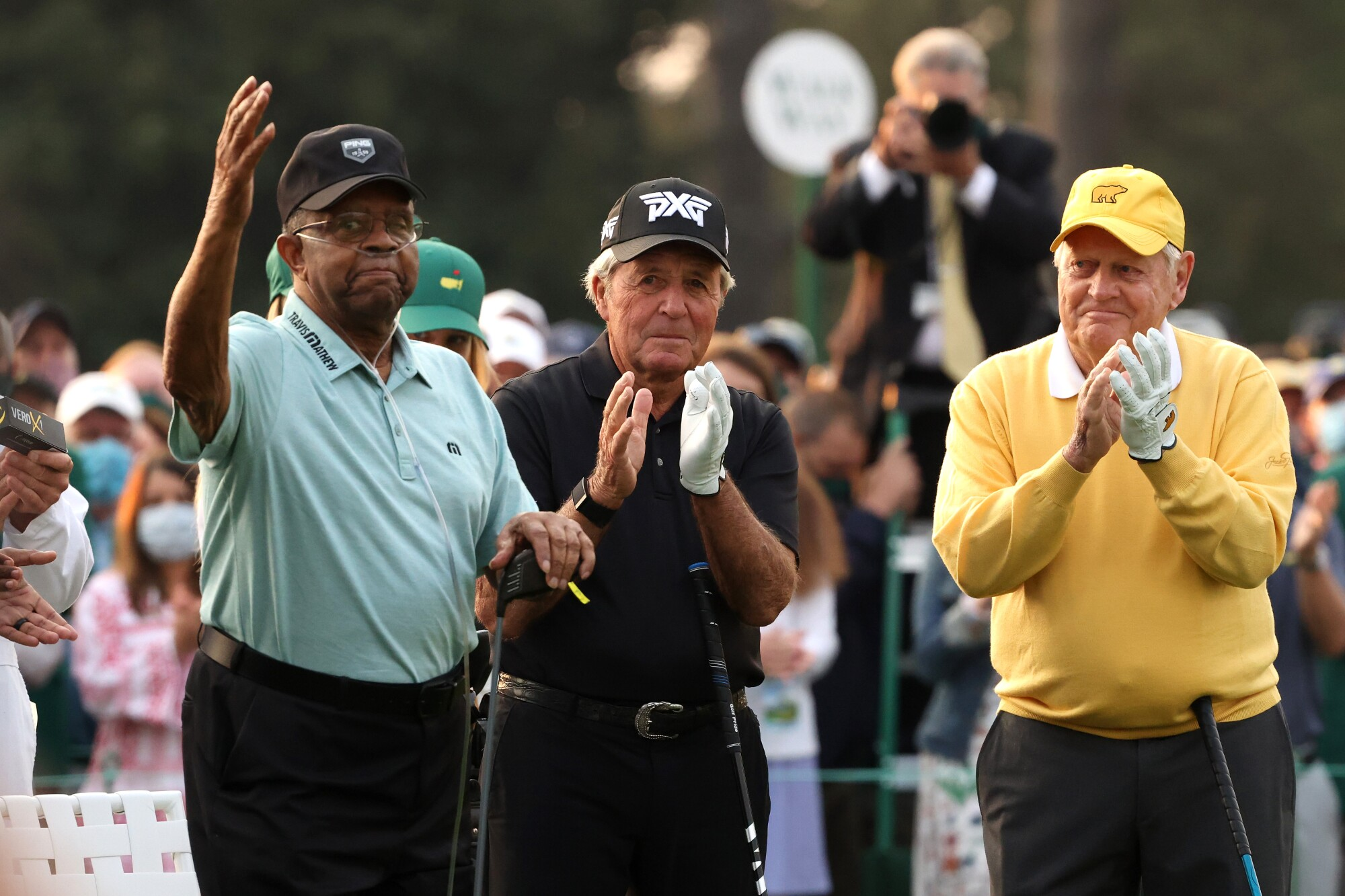 Honorary starter Lee Elder waves to the patrons alongside Gary Player and Jack Nicklaus.