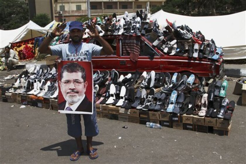 A supporter of Egypt's ousted President Mohammed Morsi waves in front of a car turned into a stand selling shoes in Nasser City, suburb of Cairo, Egypt, Sunday, July 7, 2013. Egypt's new president moved to assert his authority and regain control of the streets Saturday even as his Islamist opponents declared his powers illegitimate and issued blood oaths to reinstate Mohammed Morsi, whose ouster by the military has led to dueling protests and deadly street battles between rival sides. (AP Photo/
