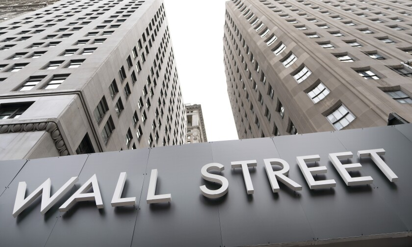 """A view of skyscrapers from below with a sign that says """"Wall Street."""""""