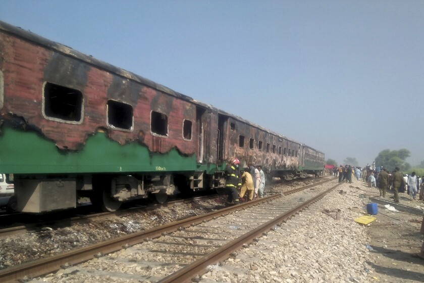 Pakistani officials examine a train damaged by a fire in Liaquatpur, Pakistan, Thursday, Oct. 31, 2019. A massive fire engulfed three carriages of the train traveling in the country's eastern Punjab province (AP Photo/Siddique Baluch)