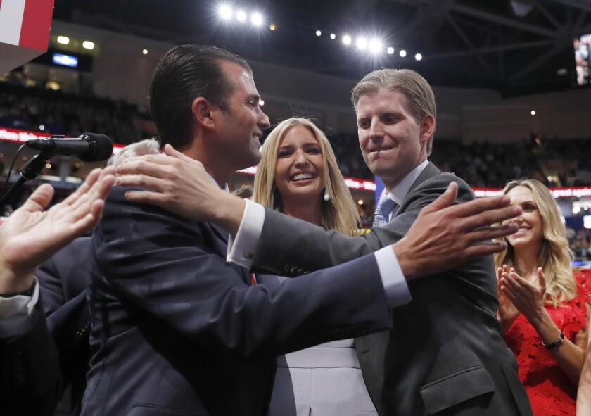 Donald Trump Jr., Ivanka Trump and Eric Trump hug at the 2016 Republican National Convention.