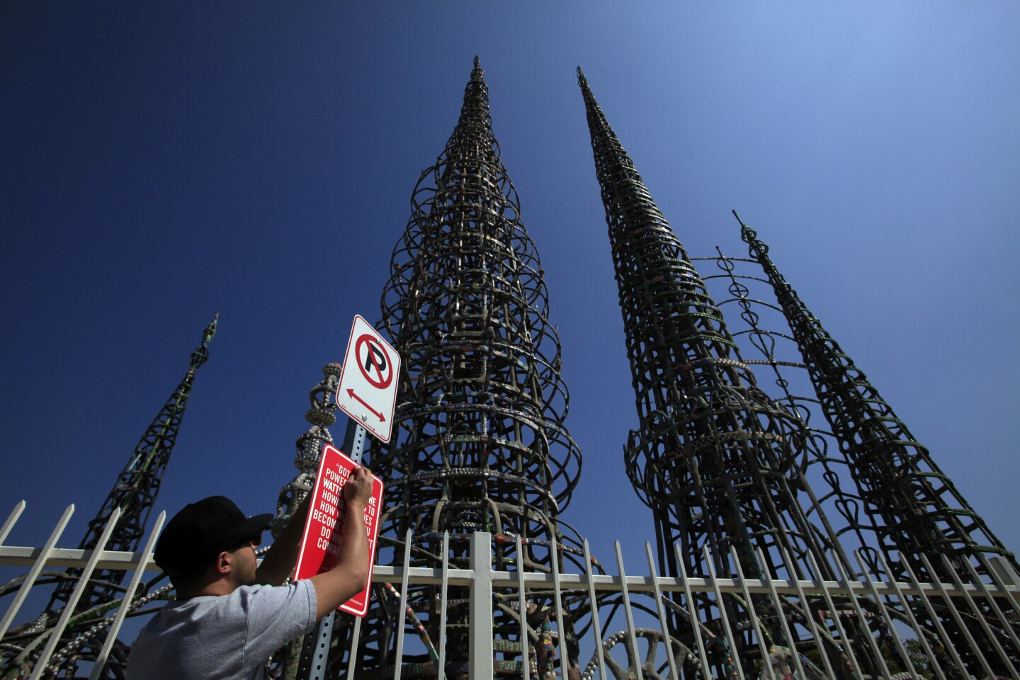 """Street artist Jason Shelowitz (a.k.a. Jay Shells) installs a sign at Watts Towers featuring rap lyrics by Crooked I: """"Got street power from the Watts Towers to Howard Hughes. How would you become me I don't Do what you cowards do."""""""