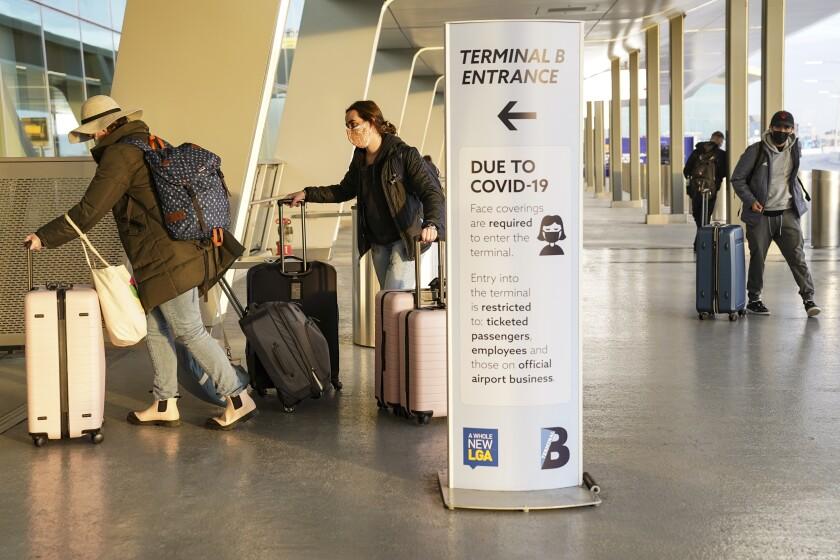 Un aviso sobre los protocolos para la prevención de COVID-19 junto a la zona de ingreso de pasajeros en la Terminal C del aeropuerto LaGuardia de Nueva York, el miércoles 25 de noviembre de 2020. (AP Foto/John Minchillo)